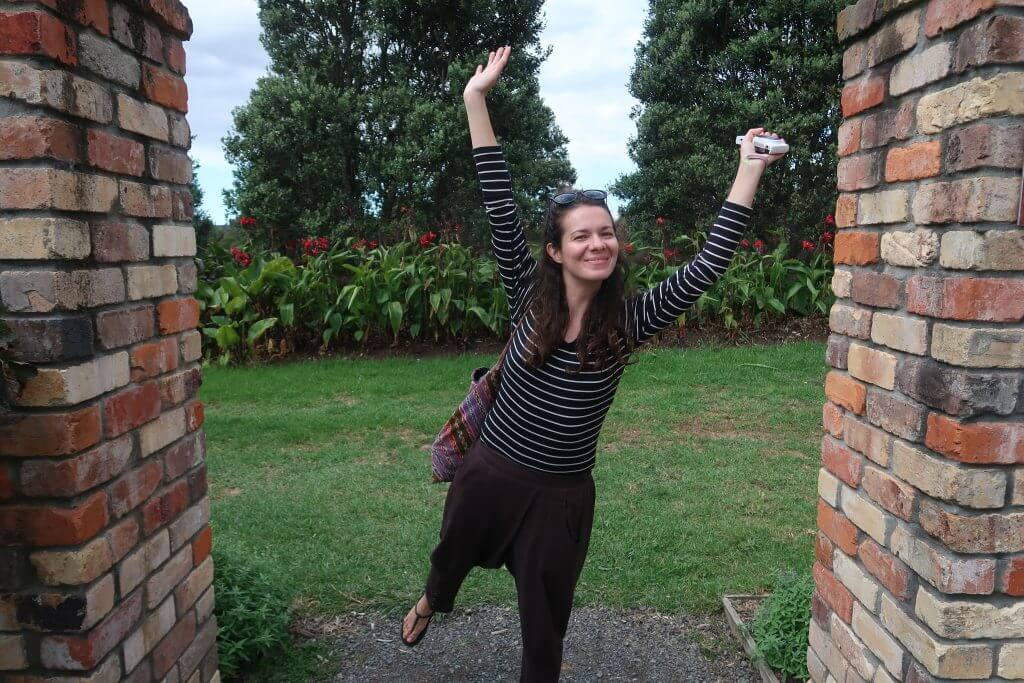 Jenny travel blogger smiling and standing on her toes with her hands up at the botanical gardens in Auckland, New Zealand