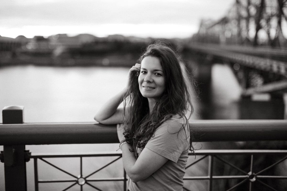 black and white image of woman standing in front of a bridge in a big city