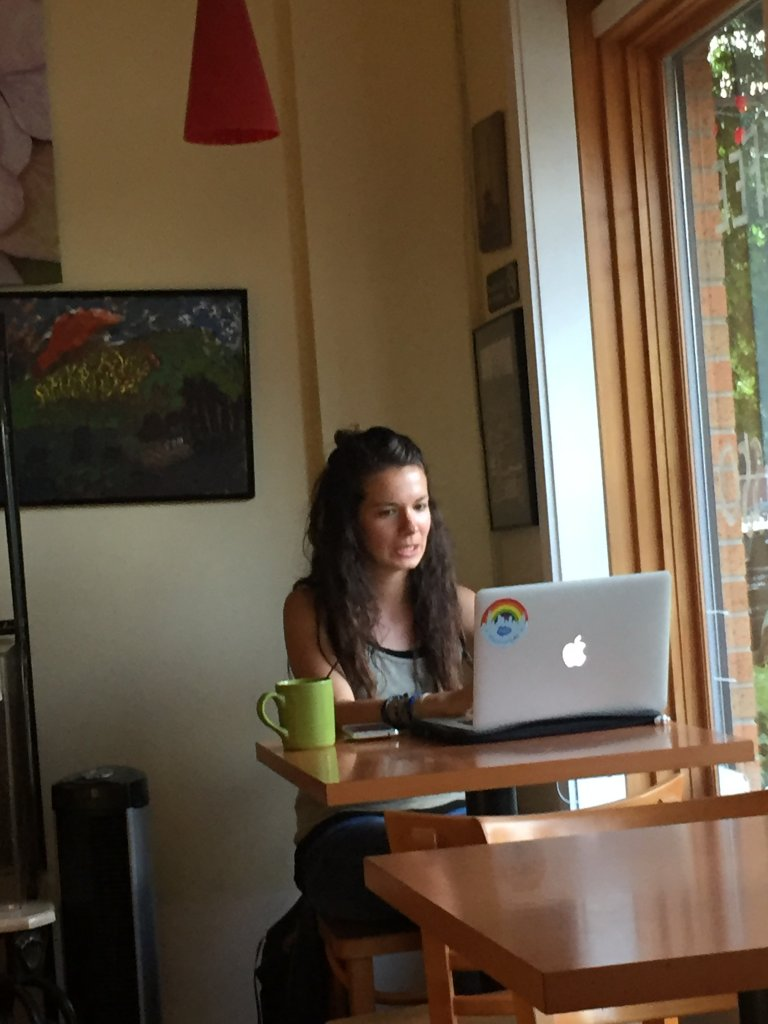freelance writer working on her laptop in a coffee shop